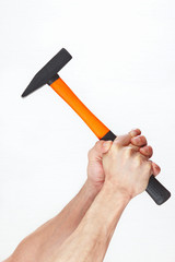 Hands of the worker holding a hammer on a white background