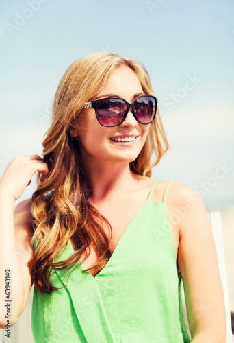 girl in shades in cafe on the beach