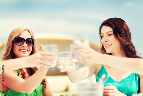 girls making a toast in cafe on the beach