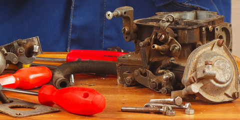 Tools and engine parts in workplace automotive serviceman