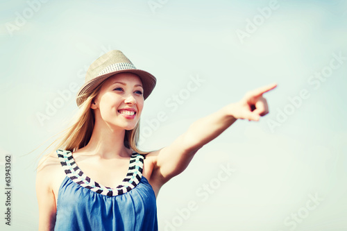 girl in hat showing direction on the beach