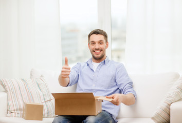 man with cardboard boxes at home showing thumbs up