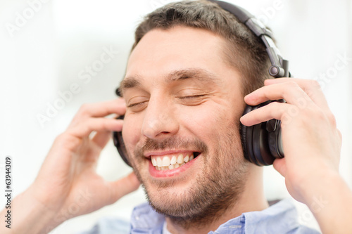 smiling young man in headphones at home