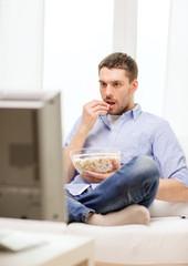 smiling man watching sports at home