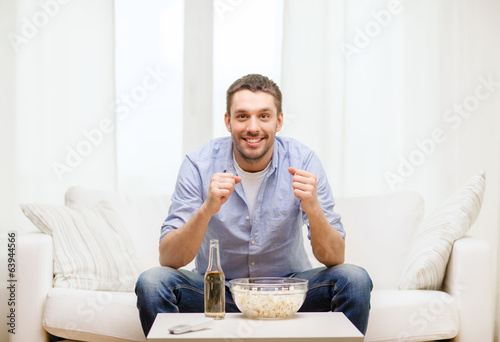 smiling man watching sports at home