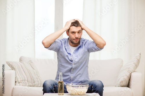 sad man watching sports at home