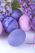 Colorful easter eggs in a basket with lilac