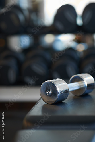 metal dumbbells lies on a bench
