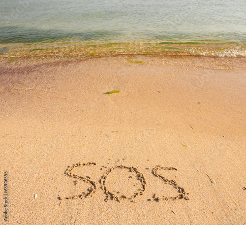 S.O.S written in the sand