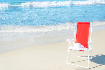 Beach chair with white hat by the ocean