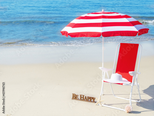 Beach umbrella and chair by the ocean
