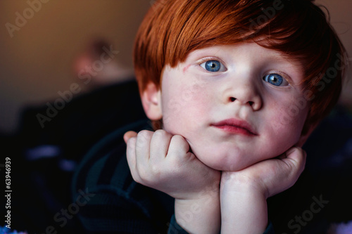 Redhead boy relaxing on bed