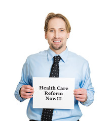 Happy business man holding healthcare reform now! sign