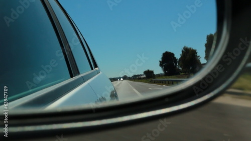 Car side mirror view driving on a freeway