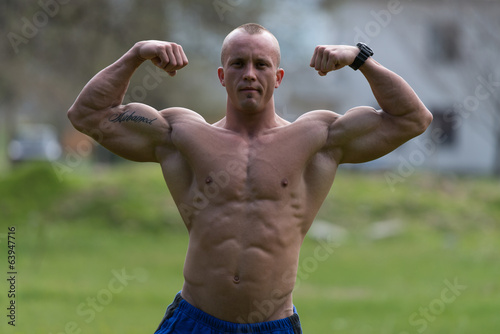 Bodybuilder Performing Front Double Biceps Poses In Park