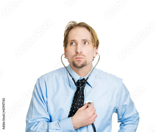 Self-diagnosis. Business man listening to his heart