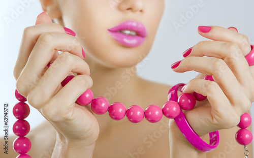 Beautiful girl with bright pink manicure and accessory close up