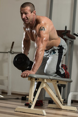 Healthy Man Doing Back Exercises With Dumbbell