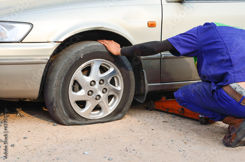 Flat tire on car with technician