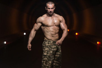 Bodybuilder Performing Side Chest Poses In Tunnel