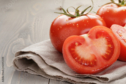 fresh ripe tomatoes with halfs on wood table