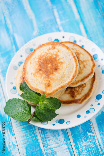 Freshly made pancakes in a glass plate, high angle view