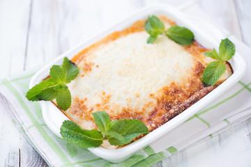 Freshly made vegetarian lasagna with mint leaves, studio shot