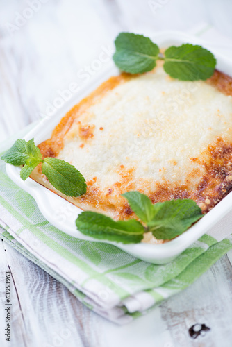 Close-up of lasagna decorated with mint leaves, vertical shot