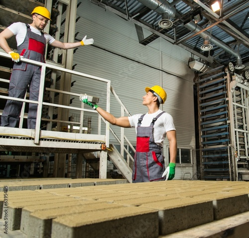 Worker and foreman performing quality check on a factory
