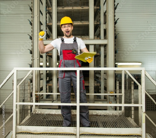 Funny worker in safety hat on a factory