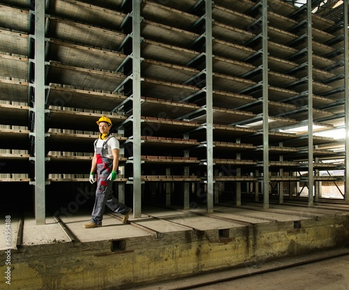 Worker in safety hat walking in a storage room on a factory