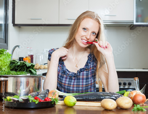 Smiling housewife is thinking how to cook  fish