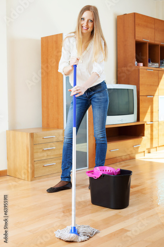 Positive blonde housewife washing parquet floor