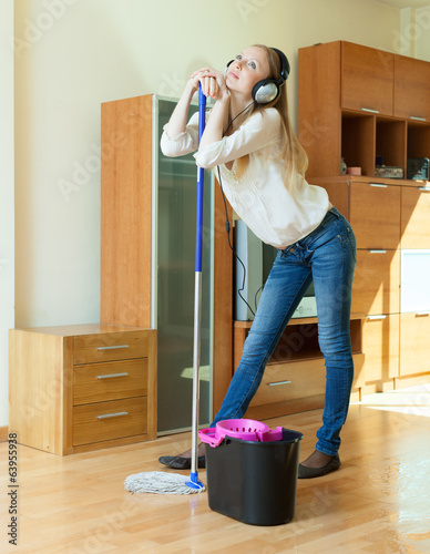 woman in headphones washing the floor