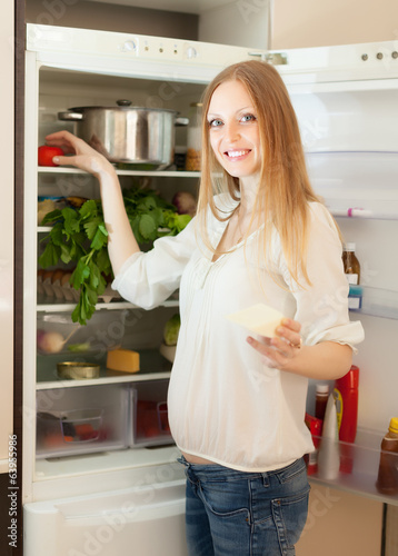 Positive woman searching for something in refrigerator