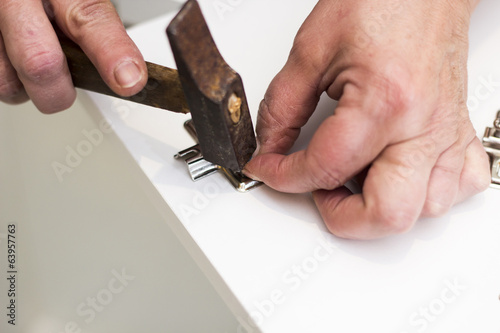 A carpenter builds a small white cabinet with a screwdriver