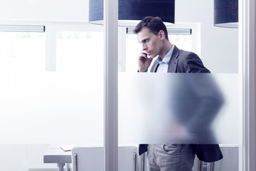Man standing in modern office calling on mobile phone