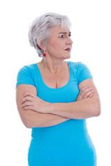 Ältere Frau in türkis isoliert blickt skeptisch zur Seite