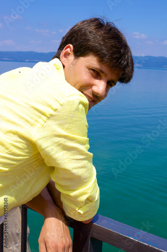 Handsome italian man smiling in vacation in front of lake