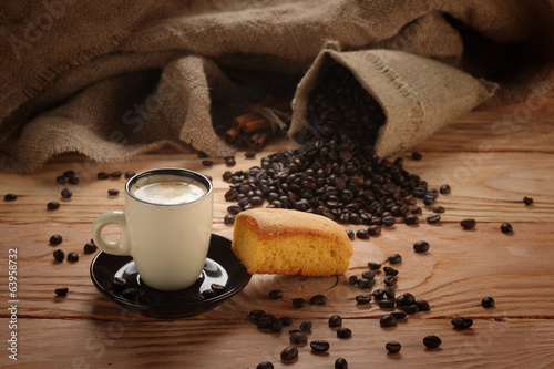A hot cup of espresso with coffee beans and Cake
