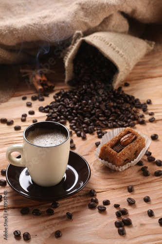 A hot cup of espresso with coffee beans and cinnamon on a wooden