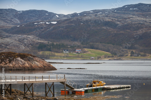 Norwegian landscape. Small motor boat stands moored near floatin
