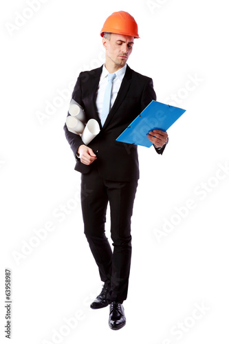 Confident businessman in helmet reading construction plan