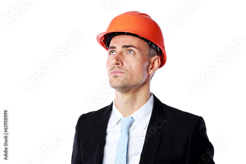 confident businessman in helmet looking up