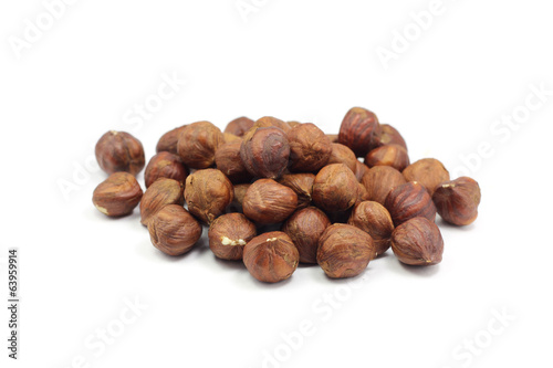 handful of roasted hazelnut kernels on a white background