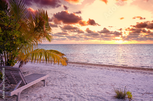 Empty chair in the tropical beach in the Maldives at sunset