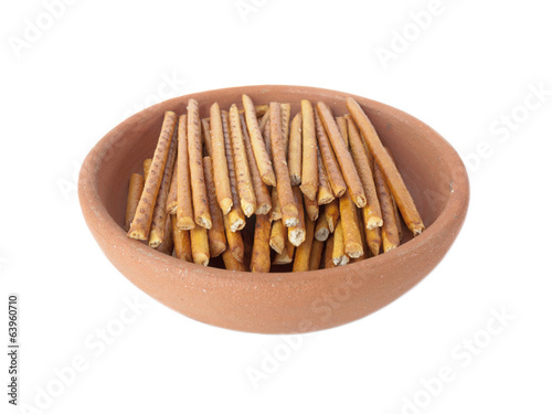 Salted sticks in clay plate isolated over white