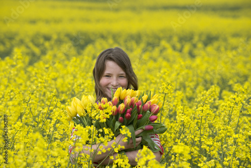 Young girl holding a bunch of Spring flowers