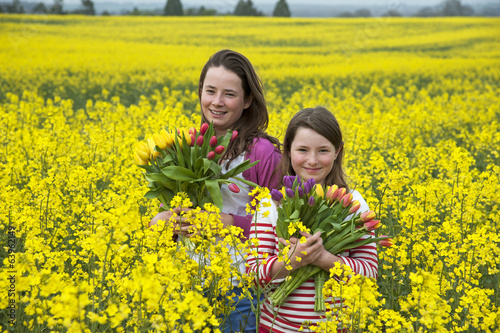 Two young girls holding Spring flowers in a field
