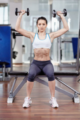 Woman working shoulders with dumbbells
